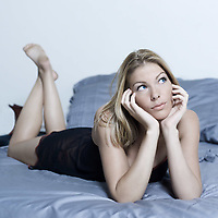 beautiful young caucasian woman lying on a bed
