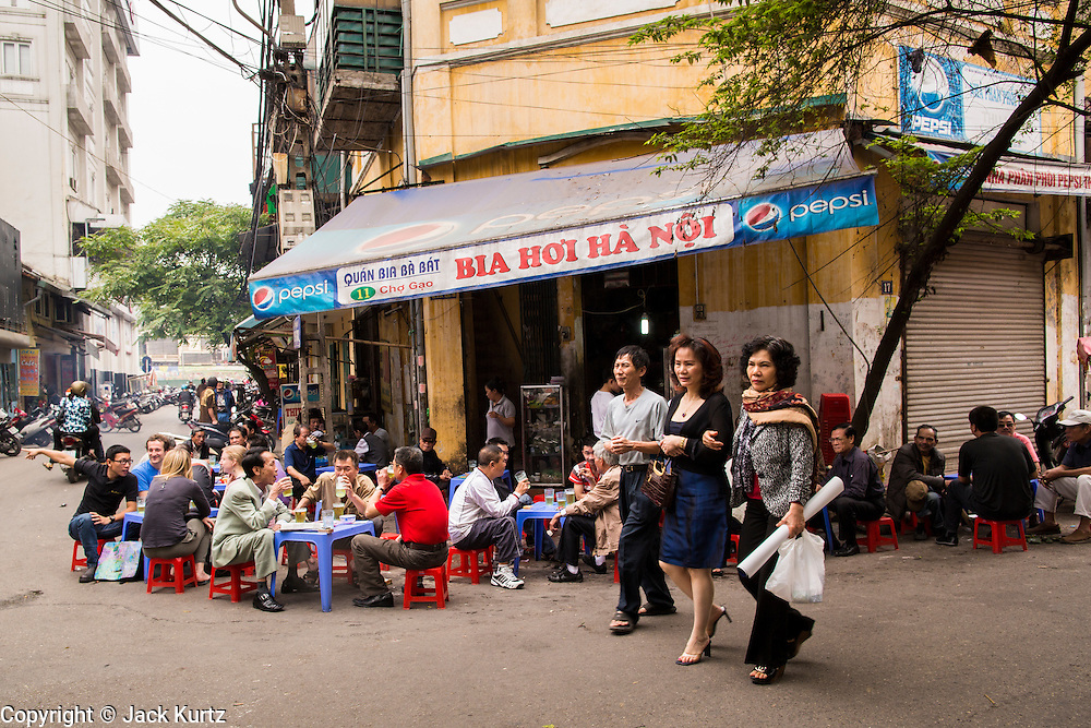 "01 APRIL 2012 - HANOI, VIETNAM:  Women walk by men drinking beer at a sidewalk cafe and beer bar in Hanoi, Vietnam. Beer, called ""bia"" in Vietnamese, costs about .20¢ US per glass at the sidewalk beer bars.    PHOTO BY JACK KURTZ"