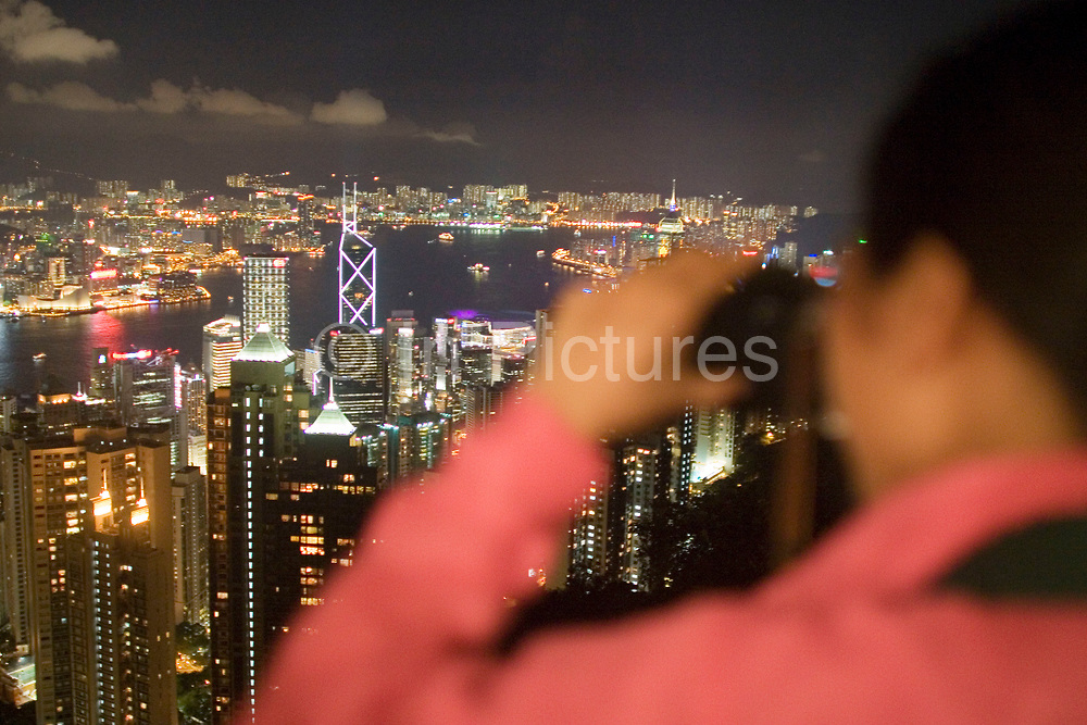 Chinese tourist takes pictures of the view from Victoria Peak viewing platform. As night falls from this classic viewpoint the entire view across Hong Kong Harbour can be seen. The view sweeping down through Mid-levels to Central, along to Causeway Bay, all the way along Hong Kong Island's coast across North Point, Quarry Bay to Wan Chai. Also over the water we see the Chinese mainland area Kowloon.