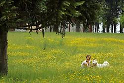 Uma menina com seu cão brincam no campo de flores.FOTO: Jefferson Bernardes/Preview.com