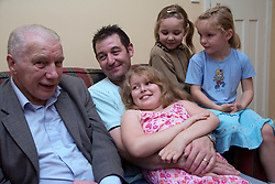 Older couple with their son and grandchildren sitting on the sofa,