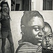 Afro Brazilian artist Gil Abelha outside his studio with his canvas
