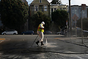 A Department of Public Works employee cleans the street in front of a homeless encampment in the Mission neighborhood of San Francisco, CA on June 25, 2020.  The encampment residents were told to relocate later that day.