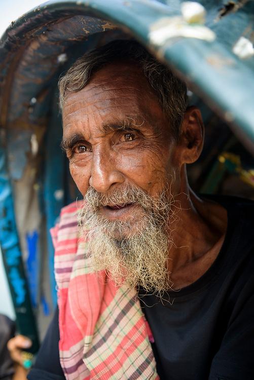 Dhaka, Bangladesh - November 1, 2017: Portrait of an 85-year-old cycle rickshaw driver in Dhaka, Bangladesh, with a grey beard and looking into the distance.
