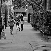 The clothes and cars may have changed, but kids have been running along this street for a ing time.  There's always an adult overseeing them, trying to keep them all in sight.