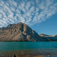 Photographers shoot dramatic clouds soaring over Crowfoot Mountain and Bow Lake in Banff National Park, Alberta, Canada.