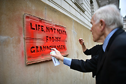 """© Licensed to London News Pictures. 07/10/2019. London, UK. Extinction Rebellion activists are seen spray painting at words """"LIFE NOT DEATH FOR MY GRANDCHILDREN"""" on the wall of The Treasury in Westminster. Activists plan to converge on Westminster blockading roads in the area for at least two weeks calling on government departments to 'Tell the Truth' about what they are doing to tackle the Emergency. Photo credit: Ben Cawthra/LNP"""