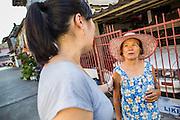 28 MARCH 2013 - BANGKOK, THAILAND:  Michelle Kao (left) talks Juan, a woman who lives in her neighborhood.    PHOTO BY JACK KURTZ