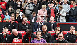 Manchester United Legends manager Sir Alex Ferguson (centre) in the dugout during the legends match at Old Trafford, Manchester.