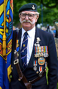 Veteran with handlebar moustache, beret, medals and flag in a parade of Veterans of the D-Day Landings at the start of the 60th Anniversary Commemorations.