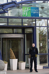 © Licensed to London News Pictures. 05/07/2020. London, UK. A Police Officer stands outside the entrance of the Holiday Inn on Bugsby's Way in Greenwich. Police were called to the Holiday Inn at 10:02hrs this morning to a report of a woman stabbed. Police Officers and London Ambulance Service attended and a woman was found suffering serious injuries and was declared dead at the scene. While attending the incident, a man believed to be known to the woman, fell from height. He was taken to hospital, where he remains under the guard of officers. His condition is being treated as life-threatening. Photo credit: George Cracknell Wright/LNP