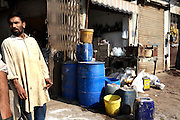 In a suburb of Lahore a trader waits for business by his shop that sells different chemicals including sulphuric acid which is used for cleaning floors, clearing drains and is the same acid that is thrown onto thousands of women each year in Pakistan.