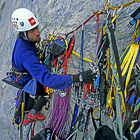 BAFFIN ISLAND, Nunavut, Canada. Mark Synnott (MR), belays from bosun's chair on north face of Great Sail Peak (Arctic big wall rock climb) as he sorts through hardware that includes cams, pitons, slings, carabiners, ropes, etc.