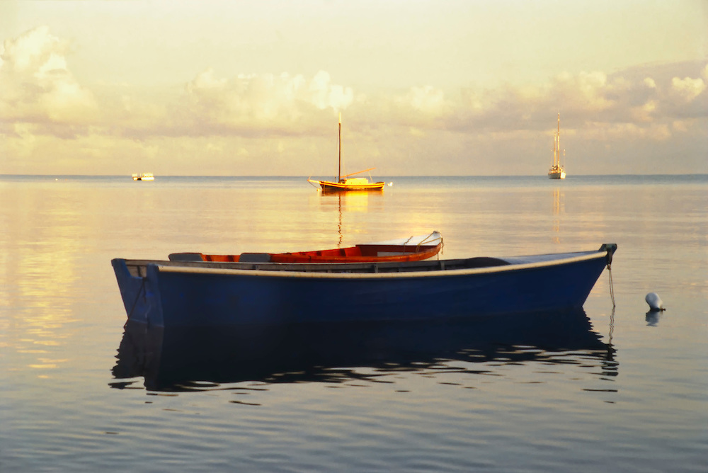 La Parguera, Puerto Rico, Small anchored boat on the calm water of Bahía La Parguera, (Bahia Bay) at sunrise. Three other boats are anchored on the horizon.La Parguera, has world-class diving and a bioluminescent bay, Small boats like this one can take several people out at night to see the glowing and flashing of silver and green lights as the water is disturbed.