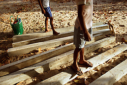 Left to right, Madu and Sivaskaran Partheepan, stand on the posts that will line the edges of the family's new land, Batticaloa, Sri Lanka, July 9, 2005. The family, who lost a 4 year old girl named Madusia, first took refuge in the Anapandi Hindu temple after their house was flattened in the tsunami. They were then moved to the Hindu college and placed in tents donated by aid organizations. Six months later, they were still living on the land where their tents were set up, but they also had a partition of their own in a tin hut with a thatched roof. With earned and borrowed money, plus a little given to them for the loss of Madusia, the family bought a small piece of land, where they plan to start anew.