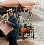 A gondolier stands reading the paper at the Ponte di Rialto, the Rialto Bridge, in Venice, Italy