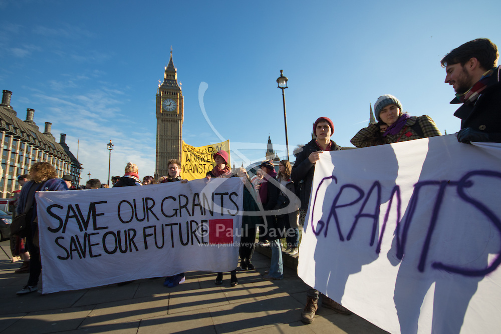 """Westminster, London, January 19th 2016. Students hold an """"emergency protest"""" in Parliament Square and later blocking Westminster Bridge, against the cutting of maintenance grants. """"It took just 18 MPs 90 minutes to scrap maintenance grants for the million poorest students, without a debate in Parliament in a backroom committee"""" PICTURED: Big Ben towers over the students and their banners. ///FOR LICENCING CONTACT: paul@pauldaveycreative.co.uk TEL:+44 (0) 7966 016 296 or +44 (0) 20 8969 6875. ©2015 Paul R Davey. All rights reserved."""