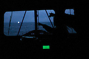 """Crew members Amber Paarman and Peter Hammarstedt, from left, point to a blinking light sighted on the horizon from the M/Y Steve Irwin's bridge on Tuesday, Jan, 6, 2009 in the Southern Ocean. The light turned out to be a Japanese whaling ship searching for a crew member lost overboard in icy waters.  When Sea Shepherd offered assistance in the search, the whaling fleet refused, saying it """"didn't need help from eco-terrorists"""". (Photo by Adam Lau)"""