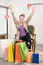 Portrait of young woman satisfied with shopping in fashion store, smiling