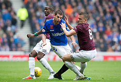 Rangers Jon Flanagan (centre) and Hearts Olly Lee battle for the ball during the Ladbrokes Scottish Premiership match at Ibrox Stadium, Glasgow.