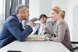 Colleagues having meeting in office, smiling