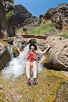 A paddler stops to enjoy hot spring water that falls into the cold Colorado River in The Black Canyon, Nevada.