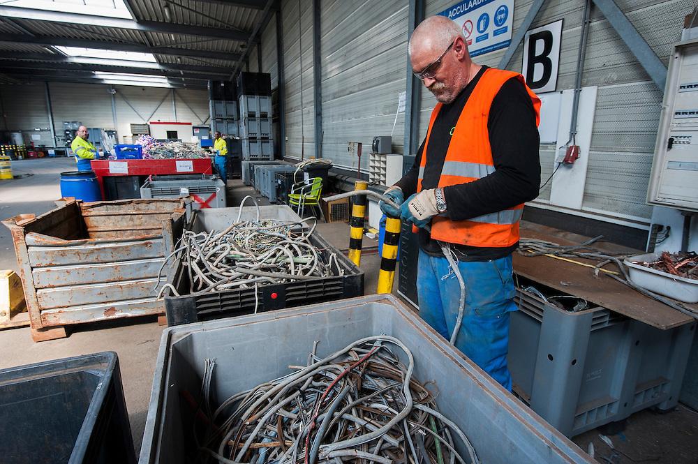 Nederland, Amsterdam, 29 aug 2013<br /> Afvalscheiding bij Afval Energie Bedrijf Amsterdam.<br /> Werkervaringsproject van Milieuwerk EcoCollege.<br /> Oude en kleine stukjes kabel worden gestript zodat ijzer en koper gescheiden kan worden. <br /> Foto(c): Michiel Wijnbergh