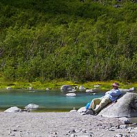 Europe, Norway, Olden. Visitor rests at Briksdal River in Jostedalsbreen National Park.