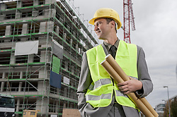 Happy male building contractor standing with blueprints and hands in pockets at a construction site, Bavaria, Germany