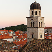 The bell tower of the Franciscan Monastery above the old city of Dubrovnik, Croatia, at sunset. <br />