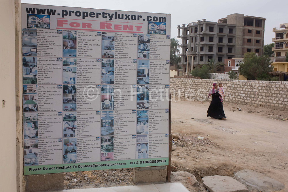 A woman and child walk past an agency's board listing details of local properties to rent in the village of Bairat, on the West Bank of Luxor, Nile Valley, Egypt. Local businesses like this are dependent of the tourism industry and therefore badly affected by the downturn. According to the country's Ministry of Tourism, European visitors to Egypt is down by up to 80% in 2016 from the suspension of flights after the downing of the Russian airliner in Oct 2015. Euro-tourism accounts for 27% of the total flow and in total, tourism accounts for 11.3% of Egypt's GDP so communities like this are suffering economically, as a result.
