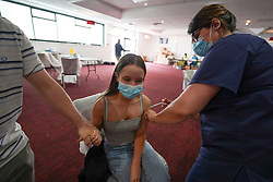 """© Licensed to London News Pictures. 10/07/2021. Sheffield, UK. Lucy Kirk, 18, receives the first dose of the Pfizer/BioNTech vaccine at a pop-up vaccination clinic at Bramall Lane, home to Sheffield United football club in Sheffield, as part of the """"Grab a jab"""" campaign. Photo credit: Ioannis Alexopoulos/LNP"""