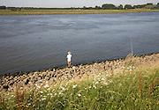 Man standing alone fishing in River Maas, Ablasserdam, Netherlands