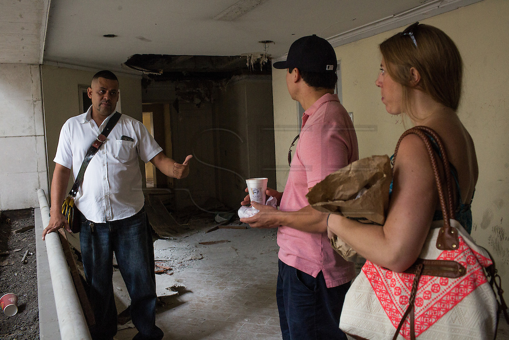 """30/03/2016 - Medellin, Colombia: Carlos Palau, a tourist guide and former policeman, talks with two American tourists, Elizabeth Wilky, 34, and Miguel Nuñez, 34,  inside the Monaco building, the former residence of notorious drug lord, Pablo Escobar. Tours focusing on the life and death of Pablo Escobar are becoming quite popular among international tourists that visit Medellín. In recent times more than 10 tour operators have started to give the tour, helped by the interest generated by Netflix """"Narcos"""" series. (Eduardo Leal)"""