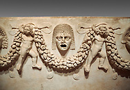 """Close up picture of Roman relief sculpted Sarcophagus of Garlands, 2nd century AD, Perge. This type of sarcophagus is described as a """"Pamphylia Type Sarcophagus"""". It is known that these sarcophagi garlanded tombs originated in Perge and manufactured in the sculptural workshops of Perge. Antalya Archaeology Museum, Turkey.. Against a grey background. .<br /> <br /> If you prefer to buy from our ALAMY STOCK LIBRARY page at https://www.alamy.com/portfolio/paul-williams-funkystock/greco-roman-sculptures.html . Type -    Antalya    - into LOWER SEARCH WITHIN GALLERY box - Refine search by adding a subject, place, background colour, etc.<br /> <br /> Visit our ROMAN WORLD PHOTO COLLECTIONS for more photos to download or buy as wall art prints https://funkystock.photoshelter.com/gallery-collection/The-Romans-Art-Artefacts-Antiquities-Historic-Sites-Pictures-Images/C0000r2uLJJo9_s0"""