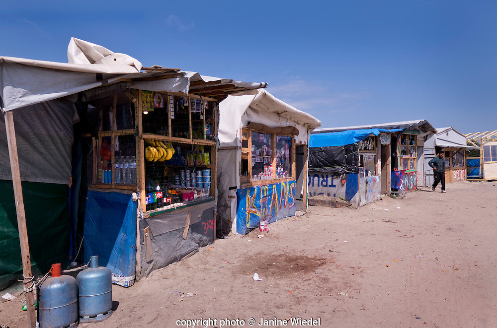 Shops built in the main walkway of the The Calais Jungle shanty town camp  housing thousands of Refugee and Migrant