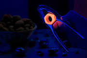 A glowing metal nut in a nut cracker. Blacklight photography.