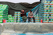 Sellers wait for customers while sitting beside boxes of fruits at a wet market in Shanghai, China on 19 January, 2009.