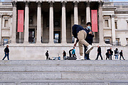 A  man bends down to pick up his bag although appearing, by a false perspective, to touch the head of a passer-by beneath the columns of the National Gallery in Trafalgar Square, on 14th October, 2021, in Westminster, London, England.