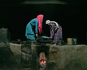 Woemn in the kitchen. Lal Ma and Bibi Hawa lifting a caldron. At the house of Arif Baig.<br /> The traditional life of the Wakhi people, in the Wakhan corridor, amongst the Pamir mountains.