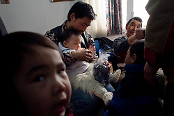 As friends and family gather and present gifts, Qipisoq Ulloriaq holds his nephew - dressed in traditional sealskin kamiks (boots), polar bear skin pants, and white canvas anorak - in his lap during a first birthday celebration for the boy. A changing climate - which shows itself in warming temperatures, earlier summers, later winters, and shrinking and thinning sea ice - threatens the livelihoods and traditions of some of the last subsistence hunters on Earth, the Polar Inuit communities of far Northwest Greenland.