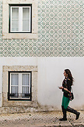 Woman passing by a house with facade decorated with ceramic tiles at Madragoa district in Lisboa.