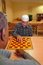 An elderly Muslim man plays draughts with a Care Assistant in a  multi-cultural elderly people's  Day Centre