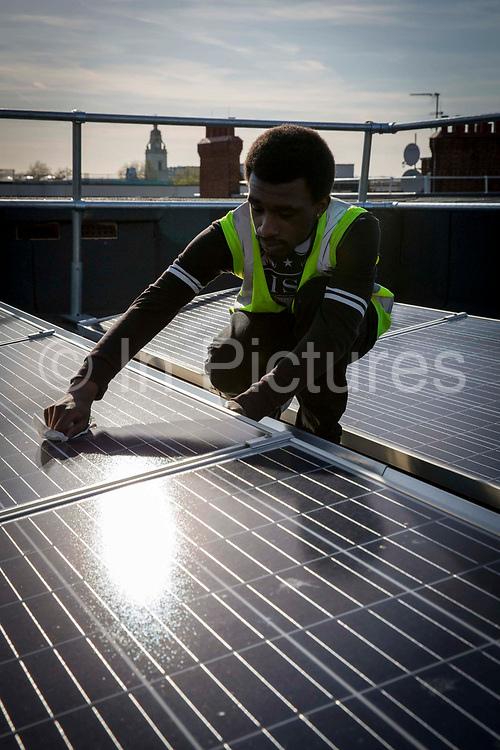 Re-Powering intern and an estate resident with the Solar photo voltaic PV panels on the roof of Hackney council estate Bannister House, the first community solar installation on a estate in Hackney, London, United Kingdom.  Bannister House was Hackney's first community solar installation, Banister House Solar, has been developed by Re-powering London in partnership with local estate residents and Hackney Council, and delivered using funds raised through a community share offer. The 102kWp solar array generates up to 82,000kWh of energy annually, saving 50,000kg of CO2 emissions. In addition, a portion of the revenue generated through the government's Feed-in Tariff and sale of energy over the 20-year life of the project will generate over £28,000 for the Banister House Solar community fund. Hackney, London.