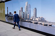 Seen from the rear, a suited businessman walks away from a a large billboard image of the Southbank of the river Thames with the tallest skyscrapers overlooking Blackfriars Bridge, on 13th September 2021, in London, England.