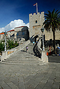 Two children (5 years old, 9 years old) running up the stairway at the Revelin Tower and land gate (Kopnena Vrata) entrance into the old town of Korcula. Korcula old town, island of Korcula, Croatia.