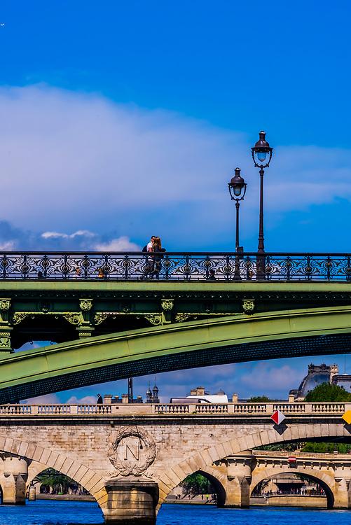 Pedestrians cross Pont d'Arcole,  one of the many bridges over the RIver Seine, Paris, France.