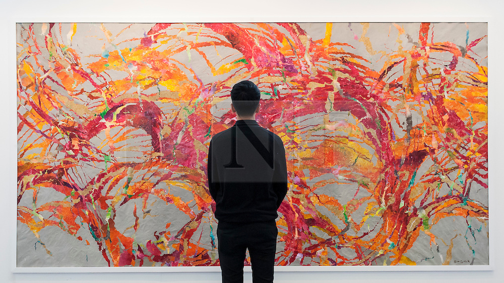 "© Licensed to London News Pictures. 19/05/2016. London, UK. A visitor looks at Qiu Deshu's ""Fissuring"". Art16 opens at Olympia, in west London.  Now in its fourth edition, the fair brings together over 100 galleries from more than 30 countries showcasing a diverse cross-section of work by contemporary artists from around the world for buyers and art enthusiasts to visit. Photo credit : Stephen Chung/LNP"