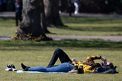 © Licensed to London News Pictures. 19/04/2021. London, UK. Members of the public relax and enjoy the sunny weather in Greenwich Park in South East London. Temperatures are expected to rise with highs of 17 degrees forecasted for parts of London and South East England today . Photo credit: George Cracknell Wright/LNP