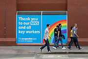 Members of the public pass a sign on the wall of a Co-Operative Bank that thanks the British NHS and key workers for their efforts during the Covid-19 pandemic on 25th July, 2021 in Manchester, United Kingdom. Community art works and murals celebrating the UKs National Health Service, its public healthcare system, have become commonplace as the public celebrate their efforts in facing down Coronavirus.